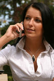 Woman networking on cell phone. Young woman using a laptop and cell phone to network Royalty Free Stock Photos