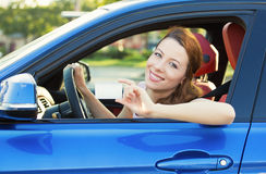 Woman in new car showing blank drivers license. Young woman in new car showing blank drivers license or sign out, through side car window. Happy lovely female Royalty Free Stock Photo