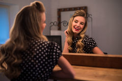 Woman with new hairstyle look in mirror in beauty salon Stock Photography