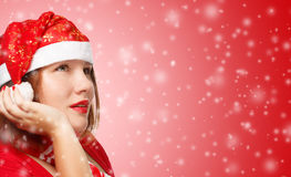 Woman in new year or christmas suit making a wish. Young woman in new year or christmas suit smiling on red background and making a wish. Close up Royalty Free Stock Photo