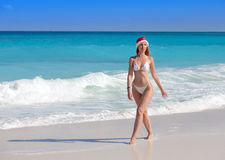 Woman in the New Year's cap walks on a beach in a sunny day Royalty Free Stock Photos