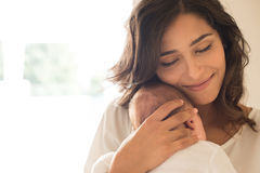 Woman with newborn baby. Pretty women holding a newborn baby in her arms royalty free stock photos