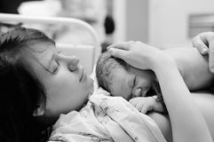 Woman with newborn baby right after delivery. Black and white shot of young women with newborn baby right after delivery Royalty Free Stock Photos