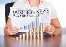Woman With Newspaper And Coins Stock Photography