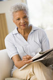 Woman with a newspaper holding eyeglasses Stock Photography