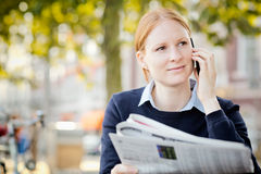 Woman with Newspaper and Mobile Phone Stock Photos