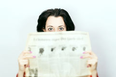 Woman with newspaper in shock Stock Photo
