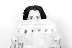 Woman with newspaper in shock stock images