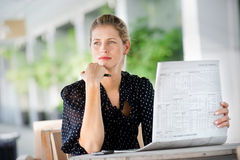 Woman with Newspapers. A young attractive woman reading newspapers at a cafeteria Stock Image