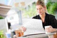 Woman with Newspapers. A young attractive woman reading newspapers at a cafeteria Royalty Free Stock Image