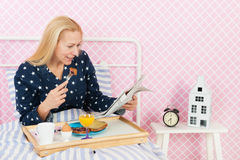 Woman with newspapers and breakfast in bed Stock Images