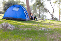 Woman next blue  tent. Stock Image