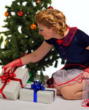 Woman next to Christmas tree. Woman sitting near a Christmas tree with gift in hand Royalty Free Stock Images
