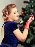 Woman next to Christmas tree. Woman decorates a Christmas tree Christmas decorations Stock Photography