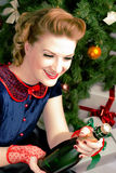 Woman next to Christmas tree. Woman sitting near a Christmas tree with champagne in hand Royalty Free Stock Photos