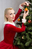 Woman next to Christmas tree. Woman sitting near a Christmas tree with balls in hand Royalty Free Stock Image