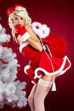 Woman next to christmas white tree on red  backgr Stock Photography