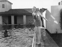 Woman next to a pool in her swimming cap and bathing suit Royalty Free Stock Images
