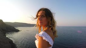 A woman next to the sea and turns to the camera and than she smiles - she is at hill and there is sunset stock video