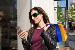 Woman next to store showcase using mobile phone Royalty Free Stock Photography