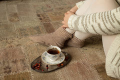 Woman next to tea cup on carpet Royalty Free Stock Image