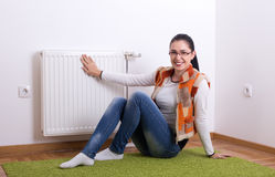 Woman next to warm radiator. Satisfied young woman sitting on the floor and holding hand on warm radiator Stock Photos