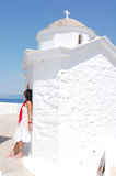 Woman next to the white church, Greece. Woman in white dress leaning on the white church, Skopelos, Greece Stock Photo