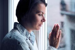 Woman next to a window looking outside in a lonely mood Stock Photo