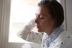 Desperate and sorrowful woman portrait next to window. Woman, next to a window, looking outside, lonely mood stock image