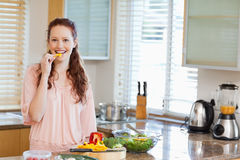 Woman nibbling bell pepper while preparing salad Royalty Free Stock Photo