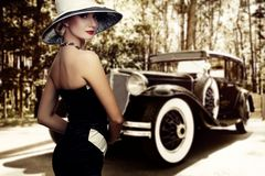 Woman in nice dress and hat against retro car stock image