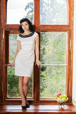 Woman in nice dress stand on sill Stock Photography