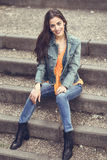 Woman with nice hair wearing casual clothes in urban steps. Young woman with nice hair wearing casual clothes in urban background. Happy girl with wavy Stock Image