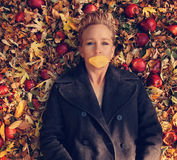 A woman in a nice jacket with a a leaf over her mouth laying in a pile of leaves and apples Stock Image