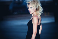 Woman at night. Blond fashion model in  black dress and punk hairstyle outdoor shot at night Royalty Free Stock Photo