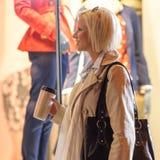Woman night city shopping window drink coffee royalty free stock image
