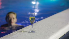 Woman at night in the pool with thermal water with a glass of champagne stock video footage