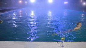 Woman at night in the pool with thermal water with a glass of champagne stock video