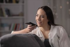 Woman in the night using phone voice recognition. Sitting on a couch in the night at home royalty free stock images