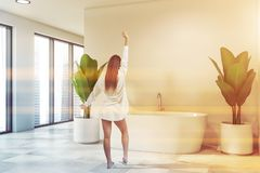 Woman in nightgown in bathroom interior. Rear view of woman in nightgown standing in stylish bathroom interior with large windows and comfortable white bathtub royalty free stock images