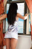Woman in nightgown looking out the window Royalty Free Stock Photography