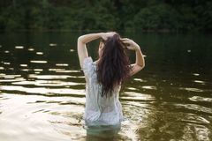 Woman in nightie is bathing in the river stock image