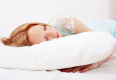 Woman in nightshirt sleeping on white pillow. In bed at home Stock Photos