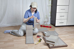 Woman nightstand assembly, bonding parts of the drawer. Stock Image