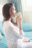 Woman in nightwear holding coffee Royalty Free Stock Photos