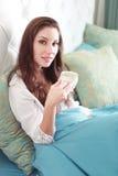 Woman in nightwear holding coffee Stock Image