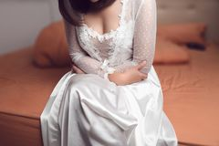 Woman in nightwear suffering from abdominal pain. Woman in white silk nightgown suffering from abdominal pain while sitting on bed in bedroom at night, Period royalty free stock images