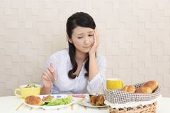 Woman with no appetite. Portrait of woman with no appetite in front of the meal royalty free stock photos
