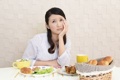 Woman with no appetite. Portrait of woman with no appetite in front of the meal royalty free stock photography
