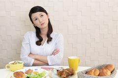 Woman with no appetite. Portrait of woman with no appetite in front of the meal royalty free stock photo